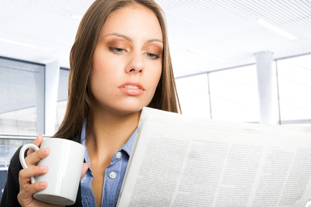 Beautiful woman reading the newspaper while drinking coffee photo
