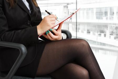 segretario: Imprenditrice prendere appunti mentre era seduto su una sedia Archivio Fotografico