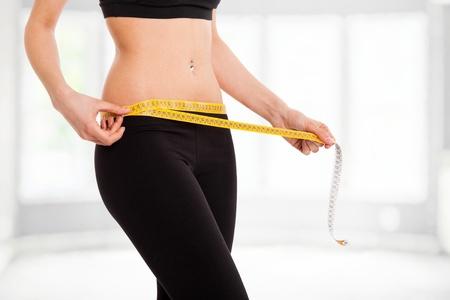 Mujer controlar sus medidas con una cinta