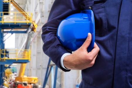 oil: Worker holding his helmet