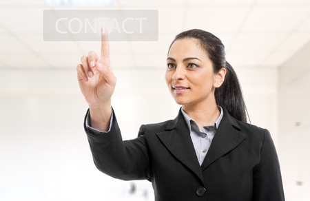 Businesswoman pressing a contact button on the screen Stock Photo - 15174182