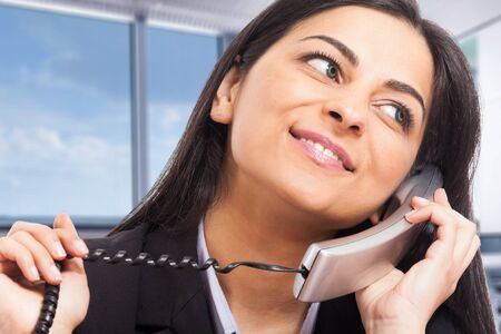 call us: Portrait of a beautiful woman talking on the phone
