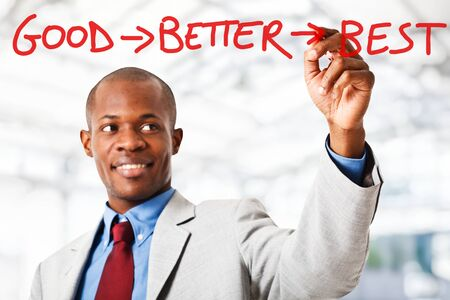 good service: Black businessman writing a motivational concept on the screen Stock Photo