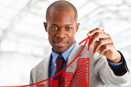 african business: Businessman drawing a positive graph