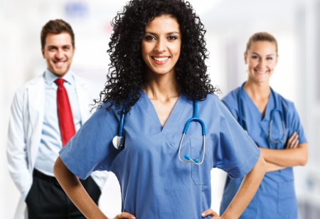 oncologist: Portrait of a smiling woman in front of her medical team Stock Photo