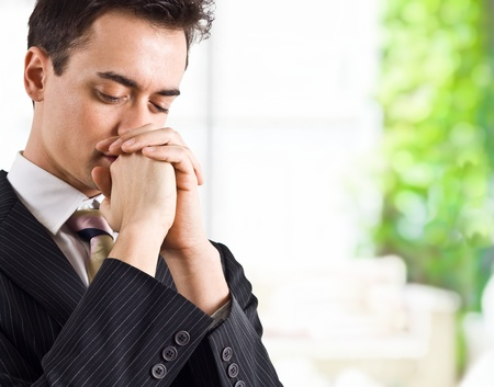prayer background: Young handsome business man praying