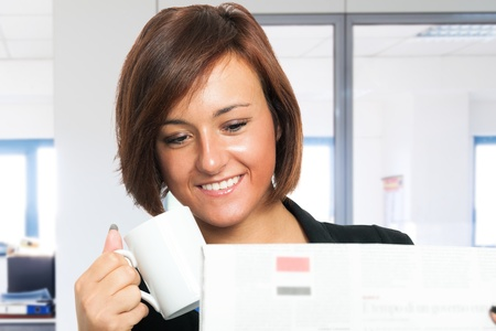 bad economy: Woman reading the newspaper while drinking coffee