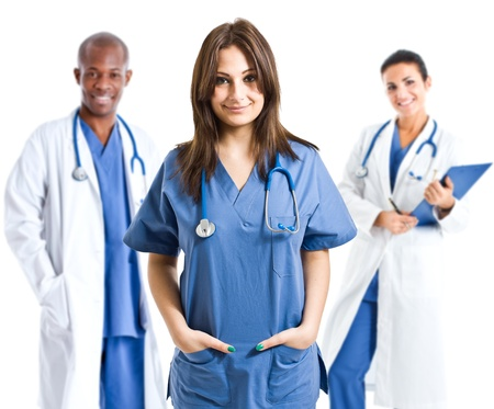 Smiling nurse in front of a small medical team photo
