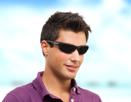 Young handsome man wearing sunglasses and a shirt smiling on the beach photo