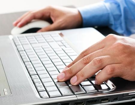 teclado: Primer plano de un trabajador que usa una computadora port�til Foto de archivo