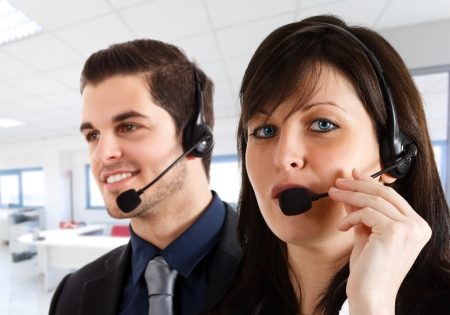 Friendly female phone operator helping a customer. Male workmate in the background. Stock Photo - 15444478