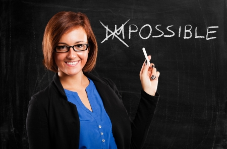 impossible: Smiling teacher turning the word impossible into possible