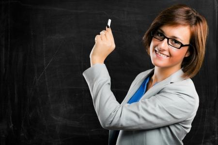 maestra enseñando: Profesora sexy delante de una pizarra vacía