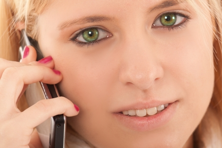Young woman with beautiful green eyes talking at the mobile phone Stock Photo - 15444540