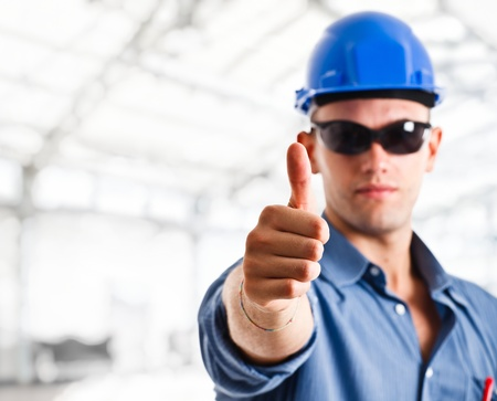Portrait of a worker doing thumbs up sign photo