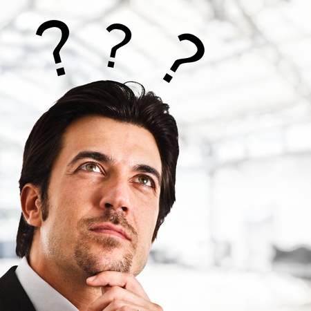 Portrait of a thoughtful man with question marks surrounding his head Stock Photo - 15444339