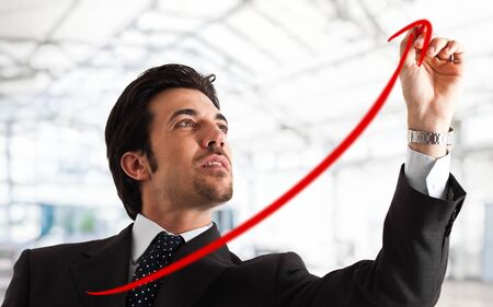 finance director: Portrait of a successful handsome businessman drawing a positive graph Stock Photo