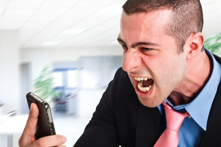 man yelling: Portrait of an angry businessman yelling at phone