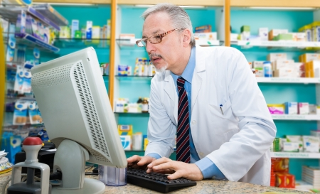 order online: Portrait of a pharmacist using a desktop computer Stock Photo