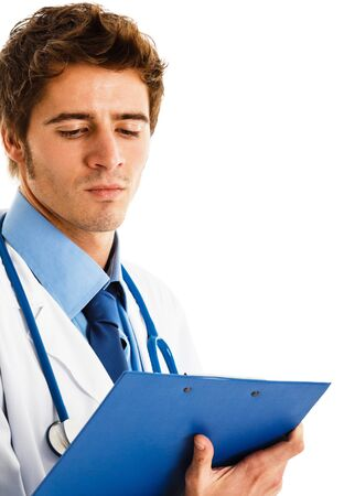 Handsome young doctor reading a case history Stock Photo - 15668196