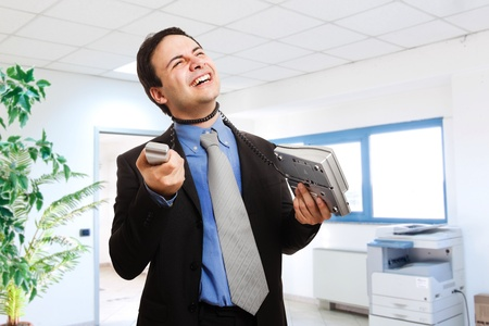 Stressed businessman strangling himself using the phone cord photo