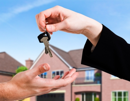 sell house: Hand passing a set of keys to another hand Stock Photo