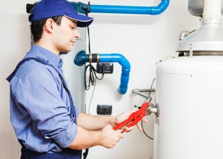 fontanero: Plumber reparar un calentador de agua caliente