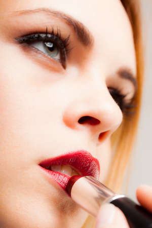 lip stick: Portrait of a gorgeous woman applying lipstick