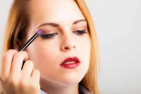 Portrait of a beautiful woman applying eye shadow photo