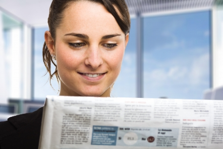 bad economy: Business woman reading a newspaper Stock Photo