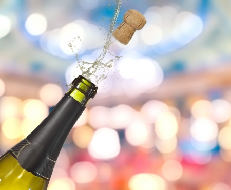 Bottle of champagne popping its cork and splashing photo