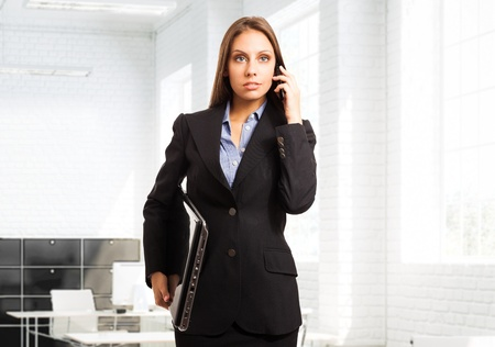 Businesswoman talking on the phone while holding her laptop Stock Photo - 15926099