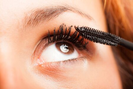 Woman applying mascara on her long eyelashes photo