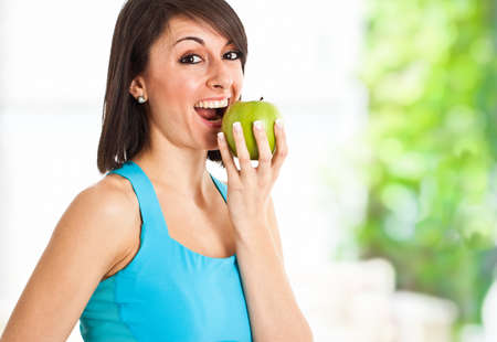 Beautiful healthy woman eating an apple photo
