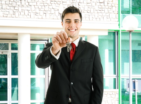 passing over: Portrait of an agent giving you the keys of your new property