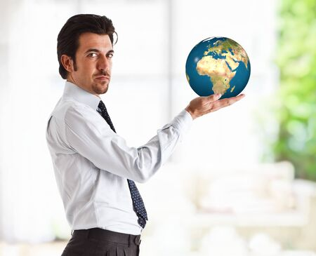 Portrait of a successful handsome businessman holding the world in the hand photo