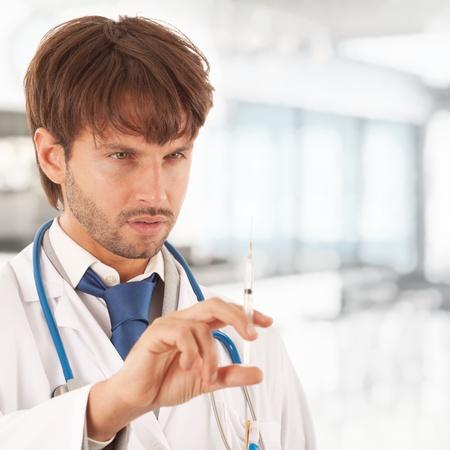 Handsome doctor examining a syringe photo