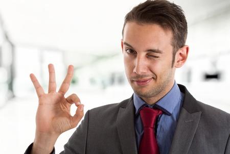 Empresario guiño a usted mientras se hace la muestra aceptable