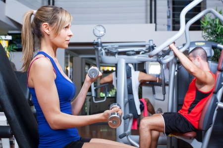 bodybuilder training: Beautiful woman working out in a fitness club