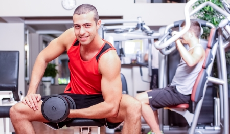 sports hall: Handsome man working out in a fitness club