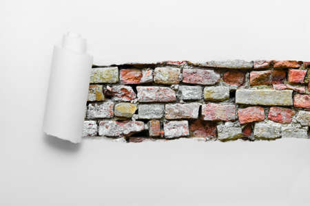 Ripped paper showing a brick wall photo