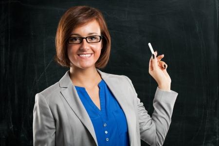 sexy teacher: Smiling teacher in front of an empty blackboard Stock Photo