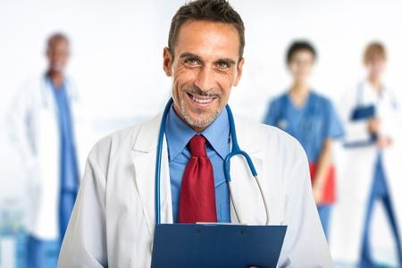 Porträt einer lächelnden Arzt vor seinem Team