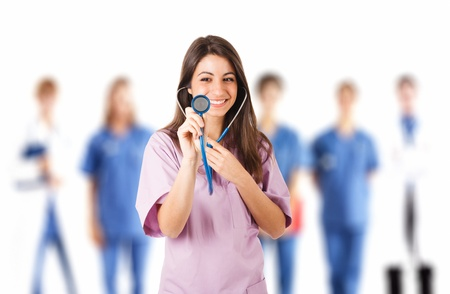 Portrait of a young beautiful nurse in front of her team photo