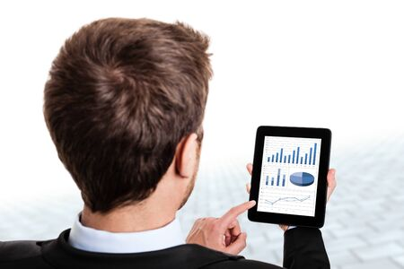 Hombre de negocios de monitoreo gráficas del mercado de valores en su tableta