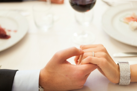 romantic evening with wine: Detail of hands in a restaurant Stock Photo