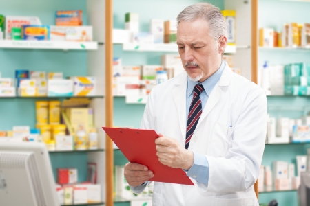 Handsome pharmacist reading a prescription photo