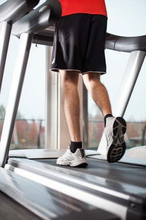 Man running on a treadmill in a fitness club photo