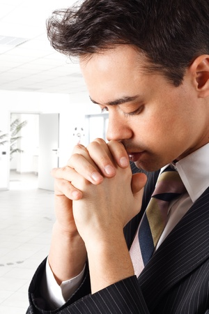 Young businessman praying in an office environment photo