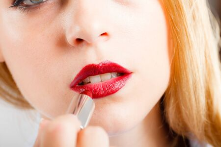 blonde  blue eyes: Portrait of a gorgeous woman applying lipstick